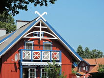 Old wooden home. Red wooden home near street in Nida , Lithuania Stock Image