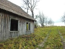 Old wooden home in village, Lithuania. Old wooden home ruins in village in autumn royalty free stock photo