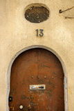 Old wooden hose door with metallic number 13 Stock Photography