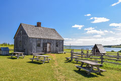 Old wooden house and benches by the ocean Stock Photography
