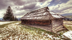 Old wooden house in the bright sky Carpathian.Hdr. Stock Photo