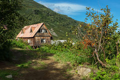 Old wooden house in brookvalley Spokoyny at the foot of outer north-eastern slope of caldera volcano Gorely. Royalty Free Stock Photography