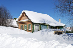 Wooden house and a car in snow drifts Stock Image