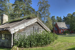 An old wooden house with a Church from the 1690s in the background in HDR. The Swedish Church Ramna and wooden house from the 1690s is placed in the open air Royalty Free Stock Images