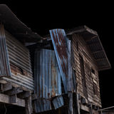 Old wooden house is damaged. Low-angle view of some old wooden houses, decayed, damaged walls with zinc deteriorate Stock Photography