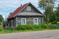 Old wooden house decorated with a pattern of old plastic lids Royalty Free Stock Photography