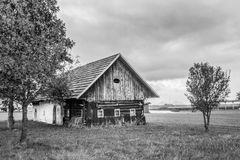Old wooden house in empty field. Royalty Free Stock Images