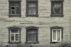 Old wooden house facade with six beautiful windows