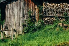 Old wooden house with fire wood on top of hill mountains in sun. Ny summer stock photography