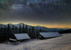 Old wooden house, hut and barn, pile of firewood in deep snow on mountain valley, spruce forest, woody hills on dark starry sky stock photos