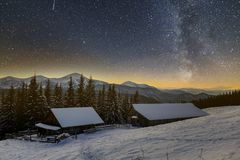 Old wooden house, hut and barn, pile of firewood in deep snow on mountain valley, spruce forest, woody hills on dark starry sky royalty free stock photo