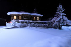 Old wooden house with a light in the window. Old wooden house with a light in the window in snow night. Night landscape in winter Royalty Free Stock Images