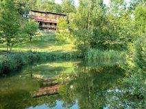 Old wooden house near a lake with reflections in water. Old wooden living house situated on a hill and a lake with reflections in water, Srebrna Gora, Lower Stock Photos