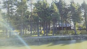 An old wooden house for rest is on the water. Video. Pond near the shore on the background of tree, nature.  stock footage