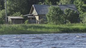 Old wooden house by the river in summer day stock footage