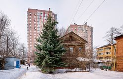 Old wooden house stands on the background of modern high-rise buildings. In the city center. Near the house grows a large green fir stock image