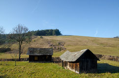 Old wooden house on sunny meadow landscape Royalty Free Stock Image