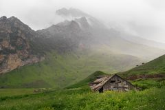 Old wooden house in the thick green grass on a background of mountains. In the fog Royalty Free Stock Photography