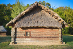 Old wooden house in the Ukrainian village. The traditional housing for the residents of the Ukrainian village. The roof is made of straw stock photo