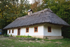 Old wooden house in the Ukrainian village. The traditional housing for the residents of the Ukrainian village. The roof is made of straw royalty free stock image