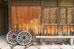 Old wooden house and Vintage wooden carriage wheel Stock Photo