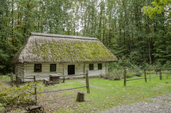 Old wooden house, white with a thatched roof covered with moss ,wallpaper Royalty Free Stock Photography