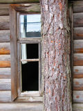 Old wooden house. Window in a log wall of the old abandoned house royalty free stock photography