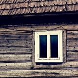 An old wooden house. A window in a wooden house. A small window in the wall of an old wooden house royalty free stock photo