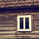 An old wooden house. A window in a wooden house. A small window in the wall of an old wooden house stock photos