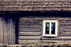 An old wooden house. A window in a wooden house. A small window in the wall of an old wooden house royalty free stock photos