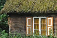 Old wooden house with wooden shutters and thatched roof. Rural buildings. Royalty Free Stock Photography