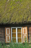 Old wooden house with wooden shutters and thatched roof. Rural buildings. Poland. Stock Photos
