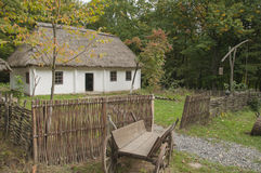 Old wooden house in the woods. Near the house, old horse-drawn background Royalty Free Stock Images