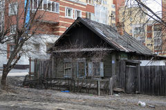 Old wooden houses against modern high-rise buildings. Tyumen, Ru Royalty Free Stock Image