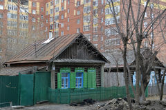 Old wooden houses against modern high-rise buildings. Tyumen, Ru Royalty Free Stock Images