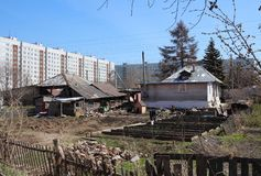Old wooden houses among multi-storey city residential buildings royalty free stock photo
