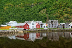 Old wooden houses with reflection at the pond, foot of the mountain in Laerdal, Norway Stock Photo