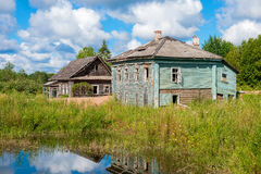 Old wooden houses on the shore of muddy pond Royalty Free Stock Images
