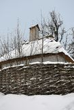 Old wooden houses under a thatched roof covered with snow and woodpile stand near old trees. stock image