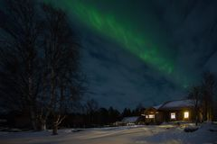 Old wooden houses in the village and the aurora borealis Royalty Free Stock Image