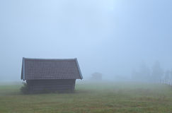 Old wooden hut in dense fog Stock Photo