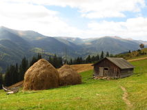 Old wooden hut and haystacks on  background of  beautiful mountain landscape and clouds. Royalty Free Stock Photo