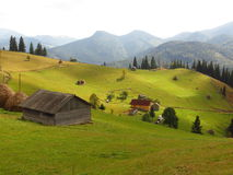 Old wooden hut and haystacks on  background of  beautiful mountain landscape and clouds. Royalty Free Stock Images