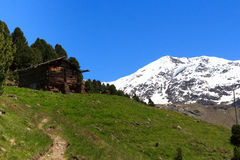 Old wooden hut, hiking path and Mountain Palon de la Mare panorama in Ortler Alps Stock Photo