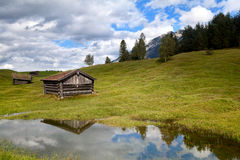 Old wooden hut by lake in Alps Stock Photos