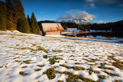 Old wooden hut on snow alpine meadow Stock Image
