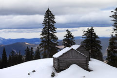 Old wooden hut in winter snow mountains at gray day Stock Photo