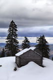 Old wooden hut in winter snow mountains and gray sky with clouds Stock Photography