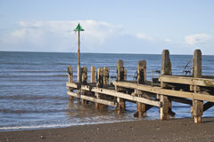 Old wooden jetty. An old wooden jetty reaching out to sea stock photo