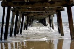 Old wooden jetty. White waves under an old wooden jetty Stock Photo